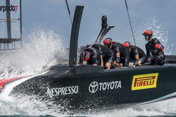 Dressed in black and wearing red helmets, America's Cup sailors pedal on board