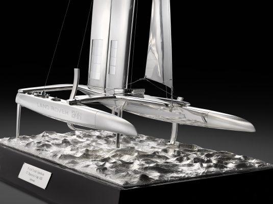 A silver sculpture of a foiling catamaran