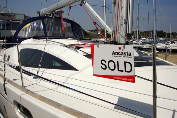 A white yacht with a sold sign on it