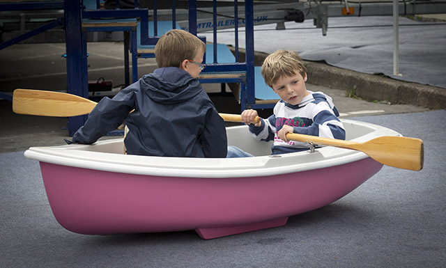 Two children pretend to row in a pink rowing boat