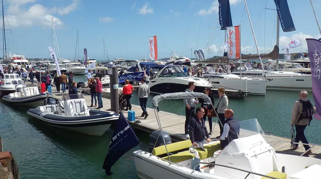 Visitors to the Poole Harbour Boat Show walk along a pontoon looking at motor boats