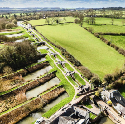 An aerial view of locks and green fields in England