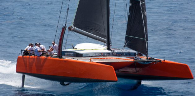 A red catamaran with black sails foiling on the water