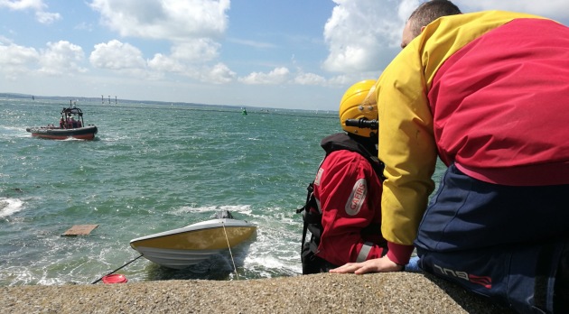 A speedboat on the rocks with two men in red and yellow jackets at Southsea
