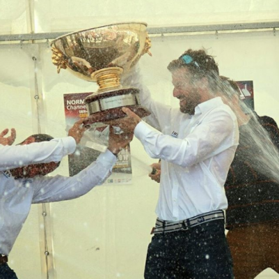 Champagne is sprayed over men as they hold a gold trophy