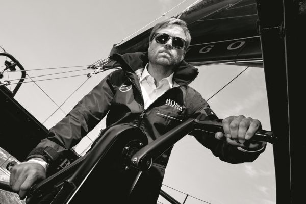 Alex Thomson wearing dark glasses helming