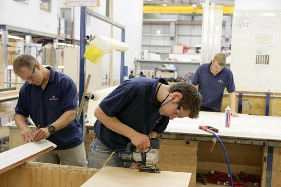 Three apprentices in t-shirts work with wood at Fairline Yachts