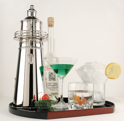 A silver cocktail shaker shaped like a lighthouse on a tray with drinks