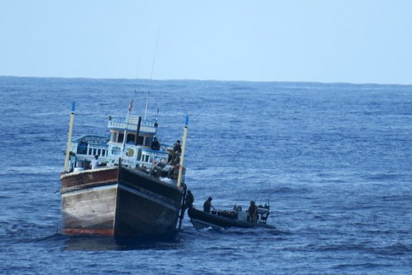 A fast RIB with crew comes alongside a fishing boat in the Indian Ocean