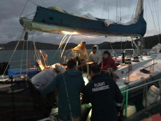 Paramedics on board a yacht in Queensland after a British tourist's leg is degloved in a yachting accident