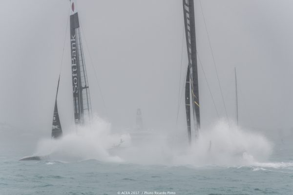 Two boats race each other with white spray