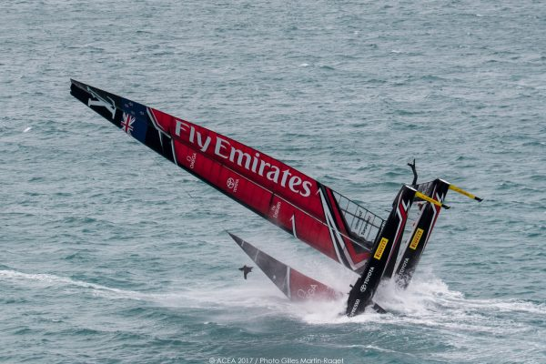 A red and black America's Cup catamaran capsizes