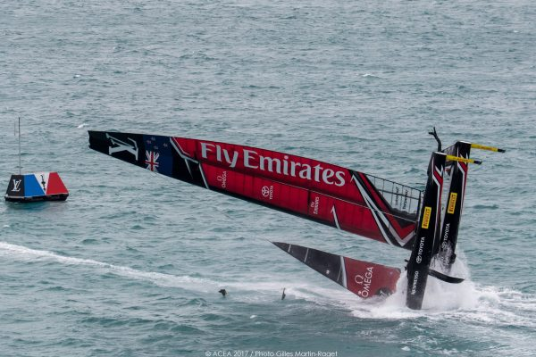 A red and black America's Cup catamaran pitchpoling