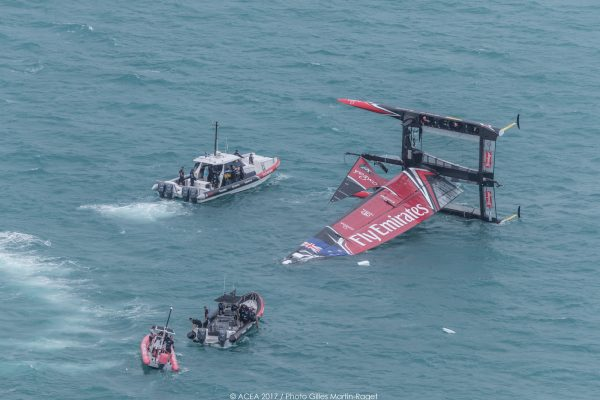 Two boats approach at capsized catamaran