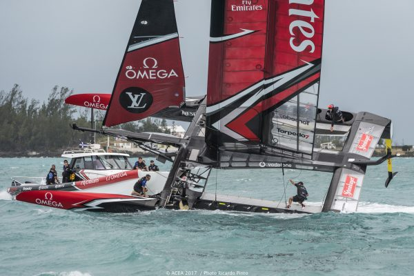 Sailors dressed in black on board a capsizing catamaran in the 35th America's Cup