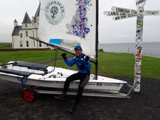 Dinghy sailor Ken Fowler with his white dinghy by the John o'Groats signpost