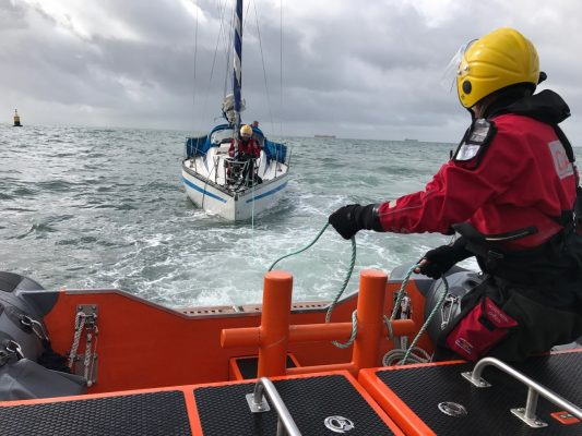 A yacht with propeller problems is towed by an orange lifeboat