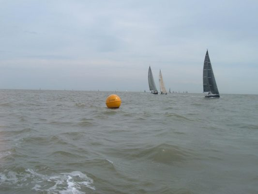 buoy in the sea with sailboats in the background