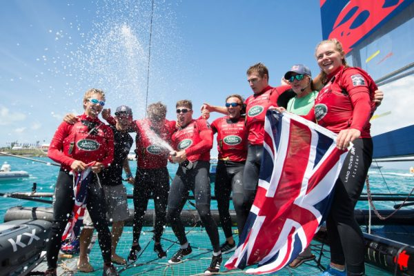 Dressed in red and holding a Union Jack flag, sailors from Land Rover BAR Academy celebrate winning the 2017 Red Bull youth America's Cup