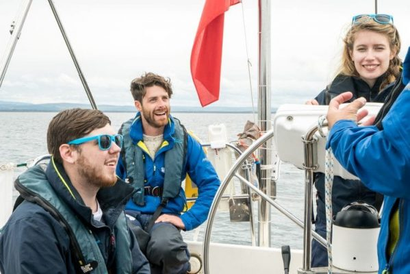 Olympic silver medallist Luke Patience, in a blue jacket, on board a yacht with young people