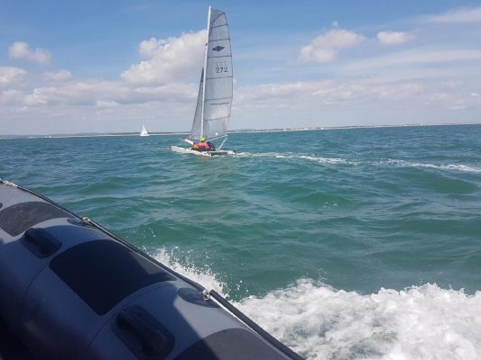 A catamaran with two people on board sailing close to No Man's Land Fort in the Solent