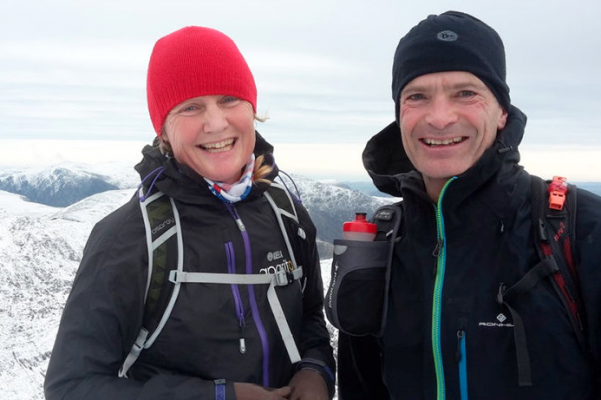 Sailing journalist Pip Hare in a red hat and Charles Hill in a black hat on top of a mountain training for the Three Peaks Yacht Race