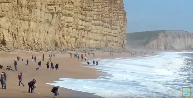 People playing on a Dorset beach ahead of a cliff fall