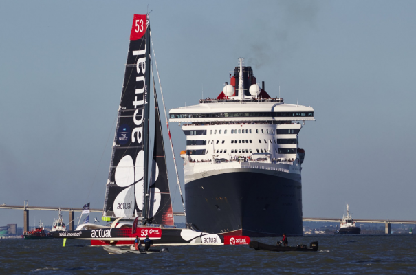 A maxi trimaran with red, black and white sails passes in front of an ocean liner