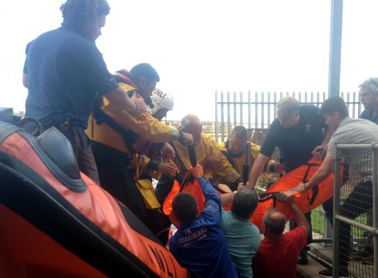 A person in an orange sling is transfered ashore after being rescue from Seaton Carew