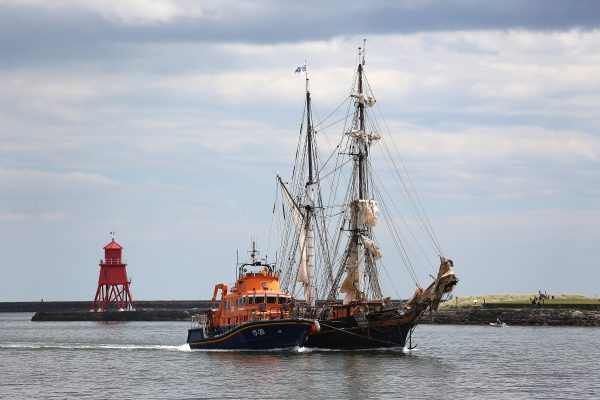 A masted sailing ship - Tres Hombres is towed by an orange lifeboat