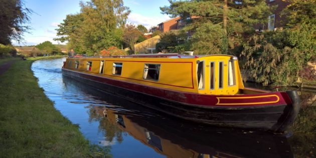 A yellow and red narrowboat on a stretch of a canal