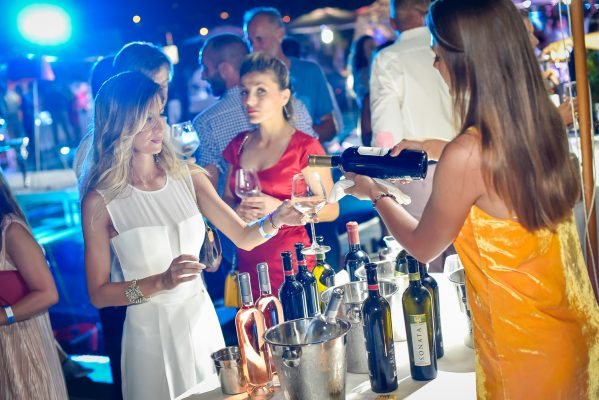 A girl in a white dress access a glass of fine wine