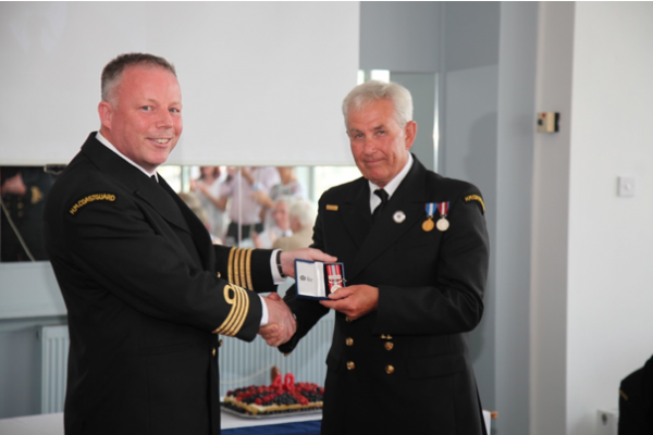 man receiving a medal from another man