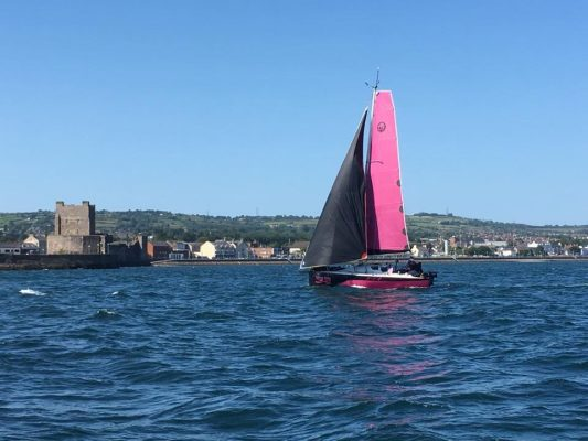 A yacht with pink sails is sailed by Natasha Lambert