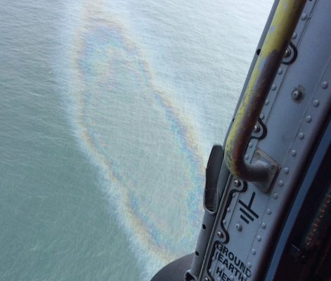 Helicopter flies over a sheen from a yacht which sank off the Washington Coast, USA