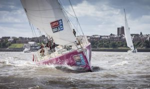 A boat with a pink hull and white sails begins the Clipper Round the World Yacht Race 2017-18