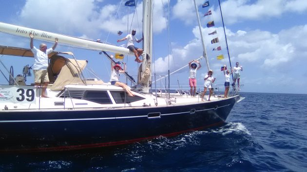 A family on a yacht wave after completing their circumnavigation