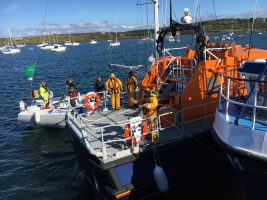 A yacht taking part in the Fastnet Race alongside a lifeboat which went to the aid of the crew when the yacht's rigging broke