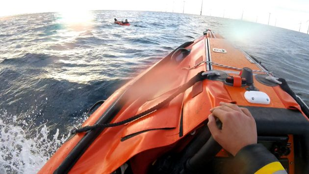 The crew of an orange lifeboat go to the aid of a man in a toy dinghy