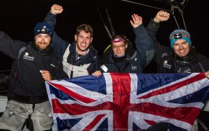 Four sailors wave a flag after beating the Length of Britain record