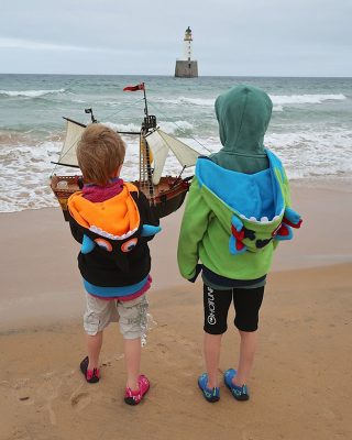 Two boys dressed in bright jumpers on a beach with a pirate ship