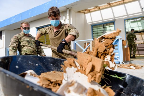 Troops wearing face masks help clear up rubbish left by Hurricane Irma