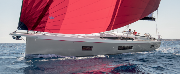A white yacht with red sails