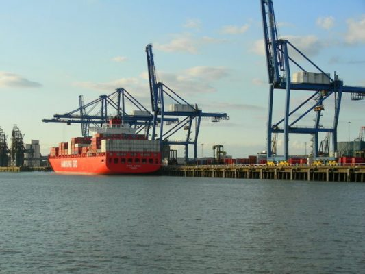 A red container ship at a port in London