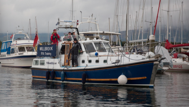 People in wet weather gear on board a motor cruiser at Scotland's Boat Show