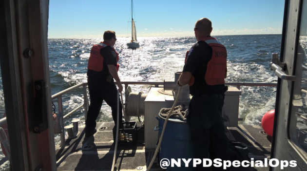 Two NYPD officers are the back of a boat towing a yacht