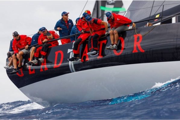 Sailors dressed in red sitting on the edge of a sailing superyacht