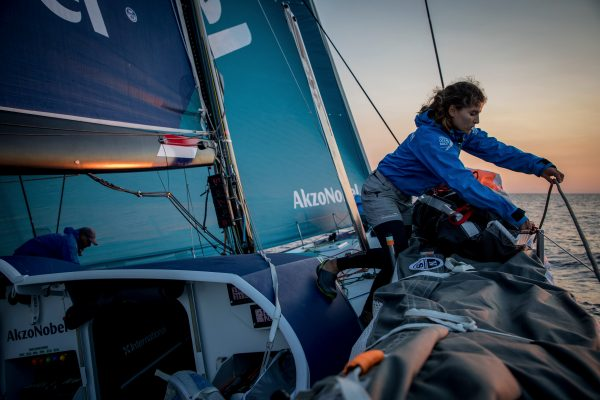 A woman sailor sorts out gear on board a Volvo Ocean Race yacht