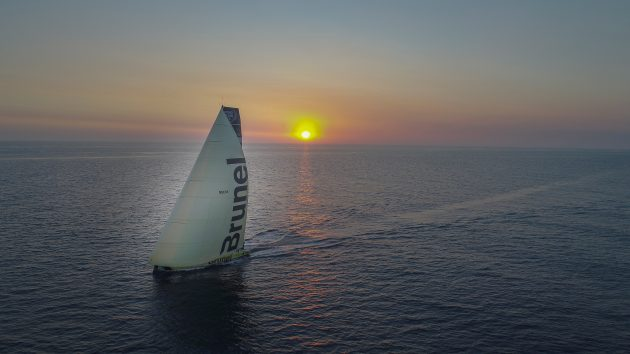 A Volvo Ocean Race yacht sailing into the sunset