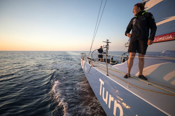 A sailor stands on a Volvo Ocean Race yacht